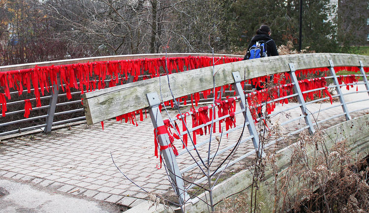 bridge with hundreds of red ribbons tied to it