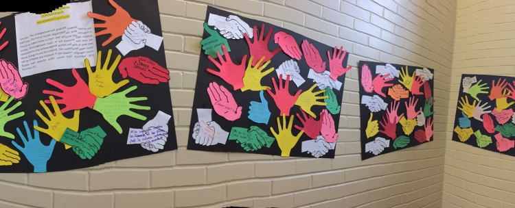 coloured paper hands cut out and stuck to wall