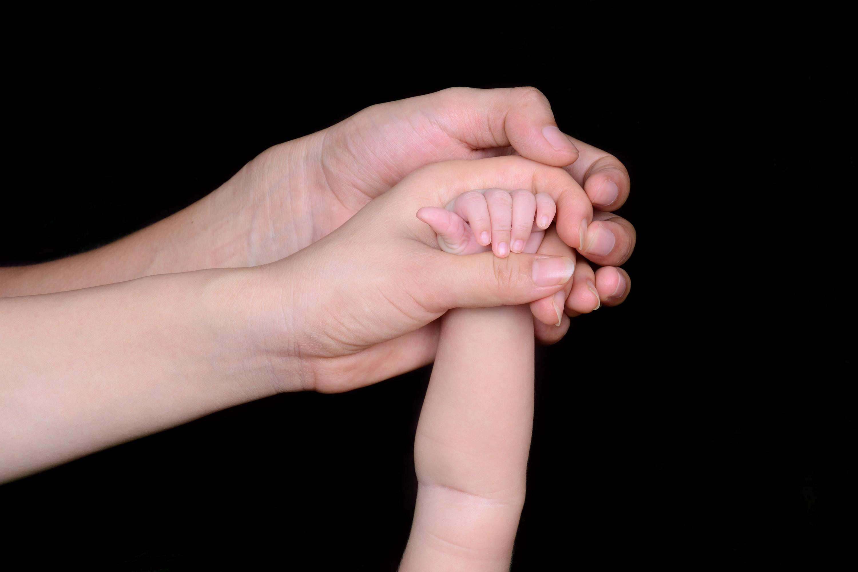 Adults holding babies hand