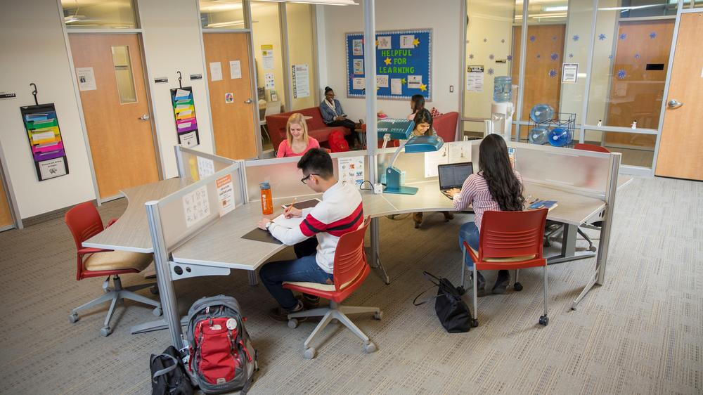 Six students sitting in a room in AccessAbility Services that has learning tools and resources for their use.