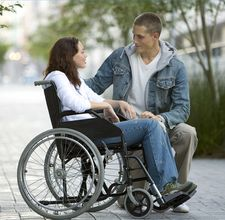 photo of a lady in a wheelchair with a support person