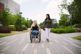 A woman walking beside another woman in a wheelchair.