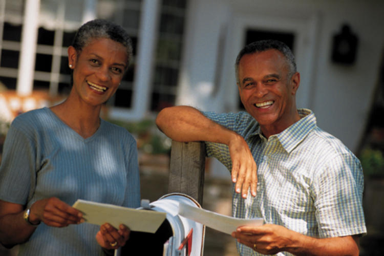 Older adult couple checking their mailbox.