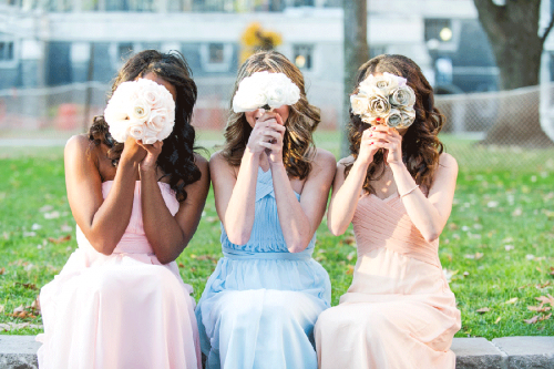 Three bridesmaids holding flowers over there faces
