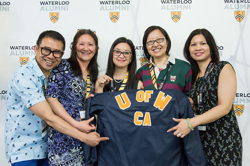 group of alumni holding waterloo jacket