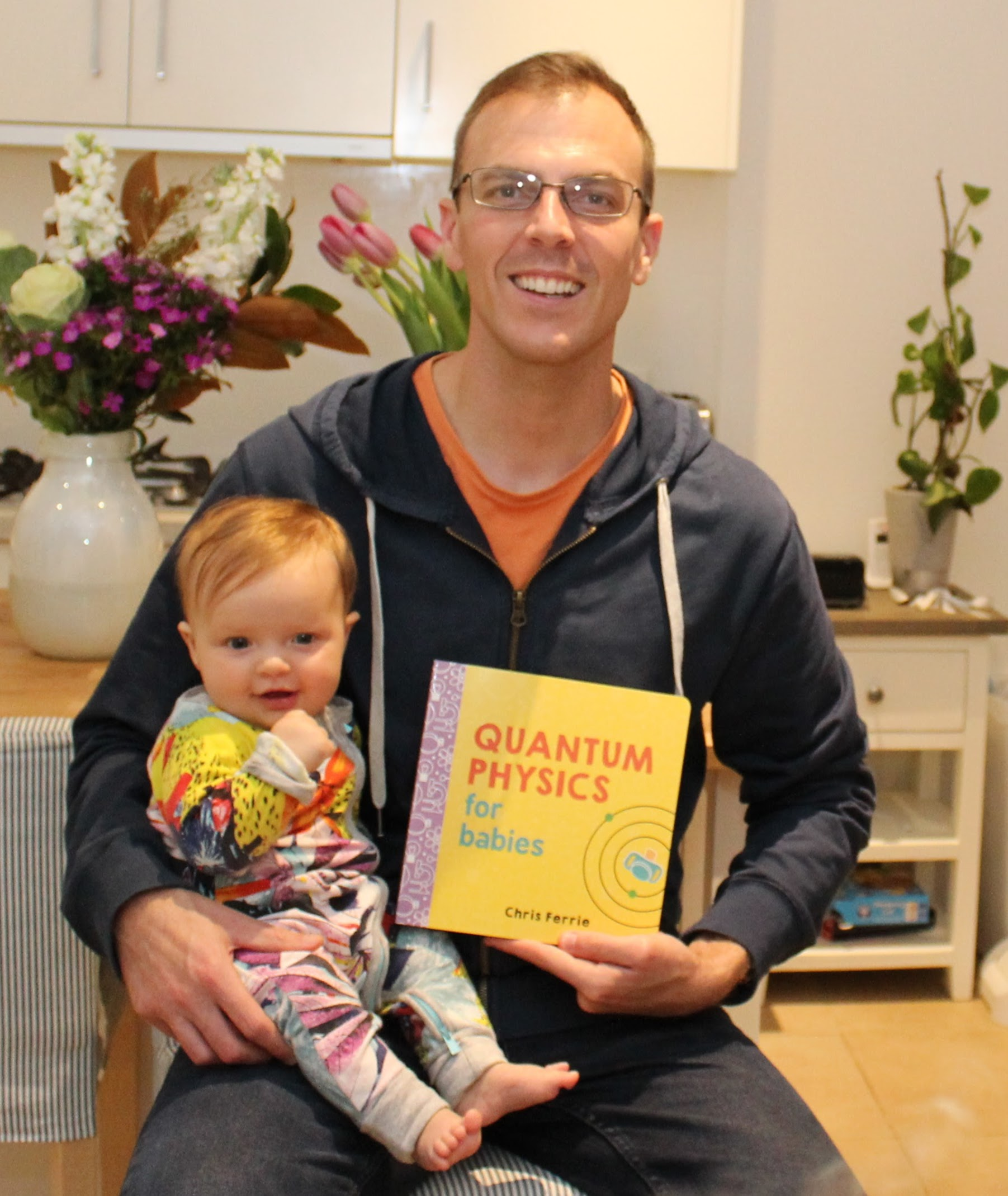 Chris with his baby and the 'Quantum Physics for Babies' book