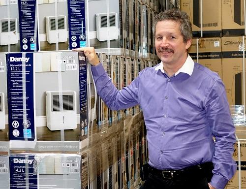 Jim Estill standing near Danby boxes