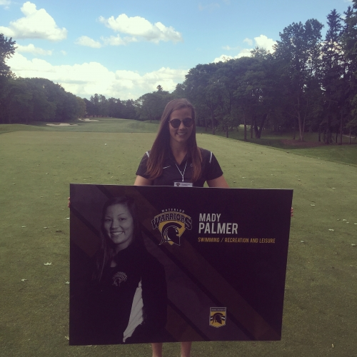 Mady Palmer on the golf course holding a sign with her face on it