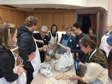 Group works together to mix kimchi ingredients.