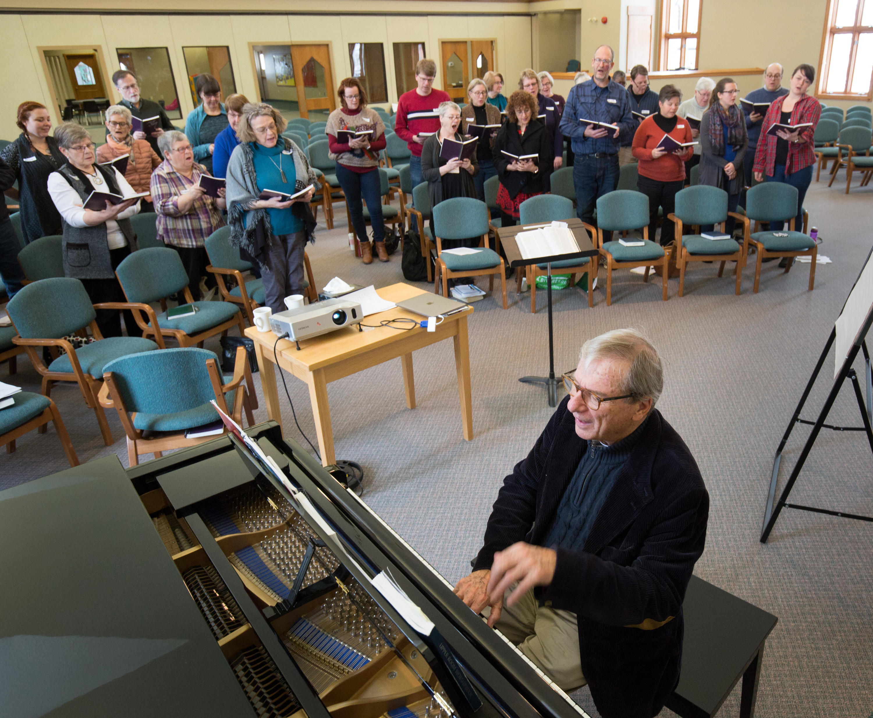 Don Saliers sits at the piano leading participants in singing from hymn books.