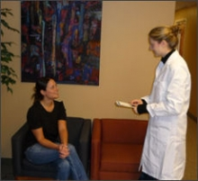 A researcher speaking to a patient
