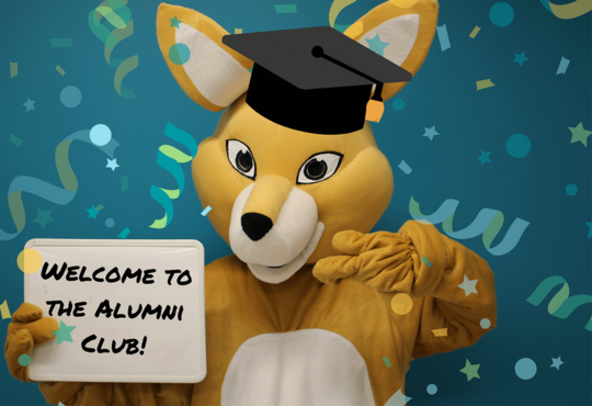 AHSSIE the A H S mascot wears grad cap and holds Welcome to Alumni Club sign.