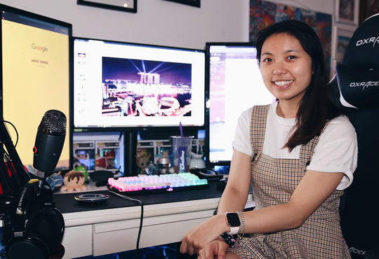 Jenny Huynh at desk with three monitors, microphone and headphones.