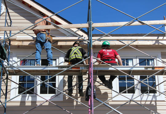 Three volunteers on scaffolding adding siding to a house.