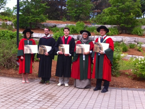graduating students posing with their degrees