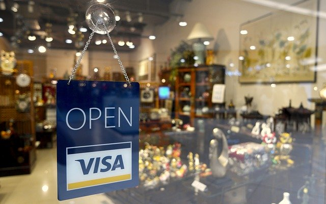 Open sign with the VISA logo in the store window of a home furnishings store