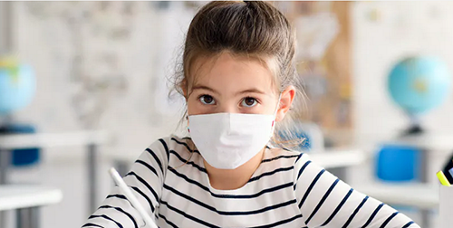 Young girl in a classroom wearing a mask