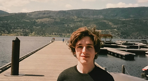 James Petrie on a dock with mountains in the background