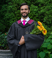 Nicholas Richardson in his convocation gown holding flowers