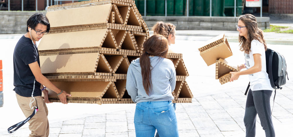 students carrying cardboard model