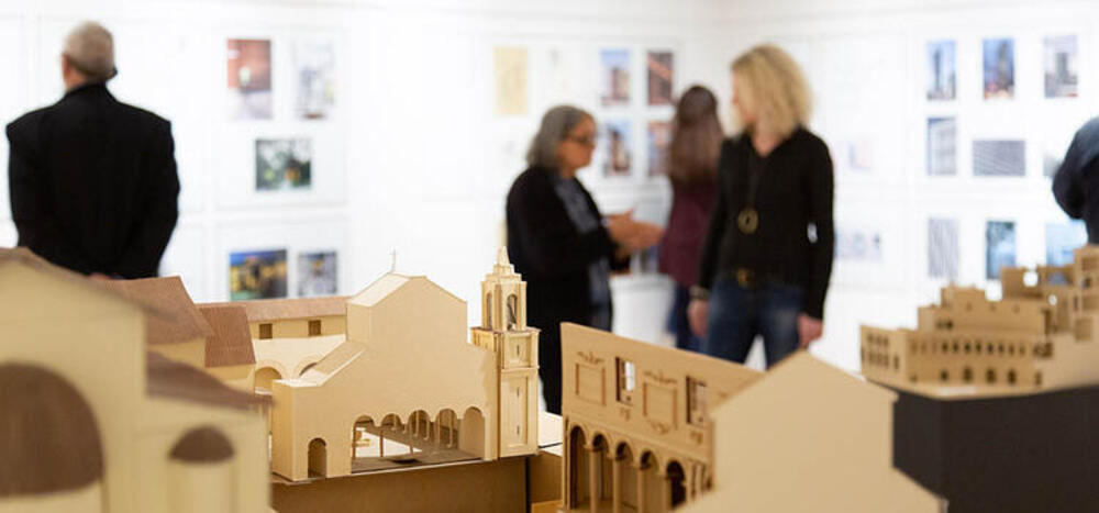 Architerctural models in forground, people out of focus in background