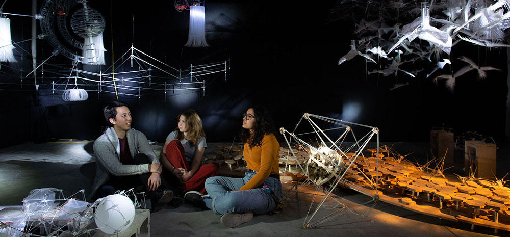 3 Students sit in a darkened room of complex interactive models