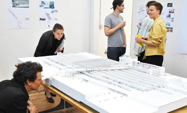 Faculty and students looking at a large architectual model