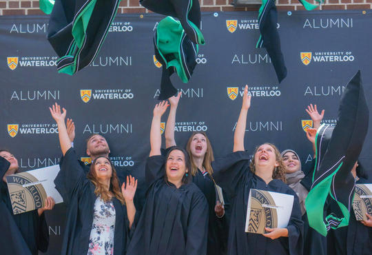 graduates laughing and throwing hoods up into the air