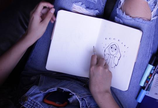person drawing in notebook on lap