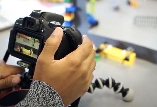 Student's hands adjusting camera for animation