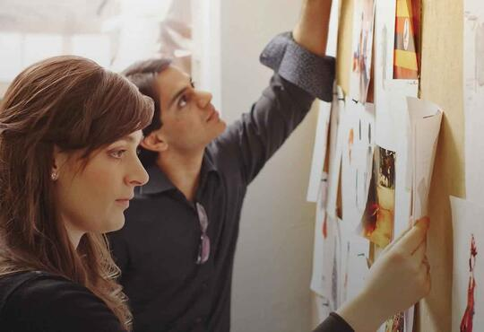 Two enterpreneurs contemplate drawings of their ideas on a bulletin board