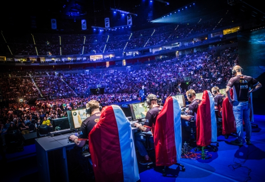 eSports players playing in front of a giant crowd in a stadium