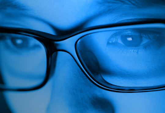 Face with glasses illuminated in blue light