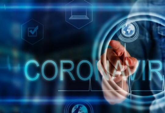 hand touching screen with coronavirus text