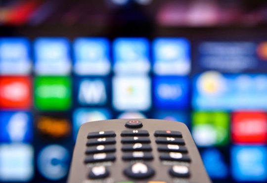 A tv remote pointed at a television