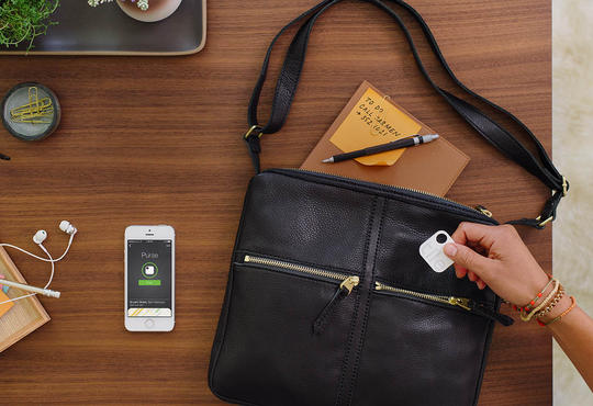 tile tracking device being put into a purse with iPhone beside it on a wooden desk