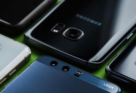 A photo of six smartphones of various brands lying face down in two rows on a green surface