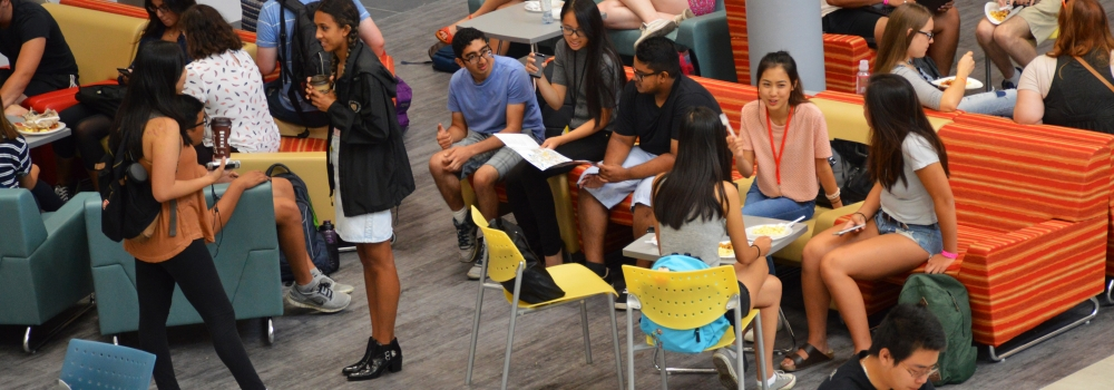 students gathered in social space with comfortable seating