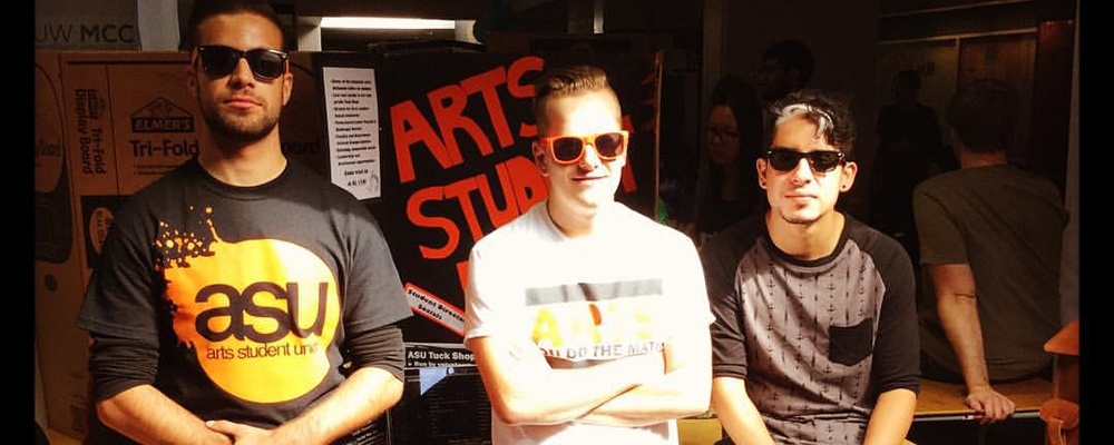 Students standing in front of the Arts Student Union booth