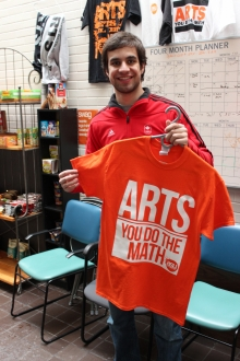 Arts Student Union member holding up an orange shirt.