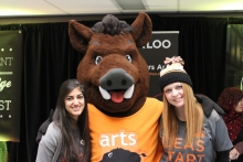 Two arts students standing with the arts mascot.
