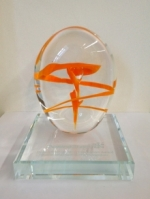 award sculpture made of clear glass with swirl of orange