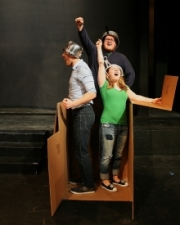 three poeple in a box on stage