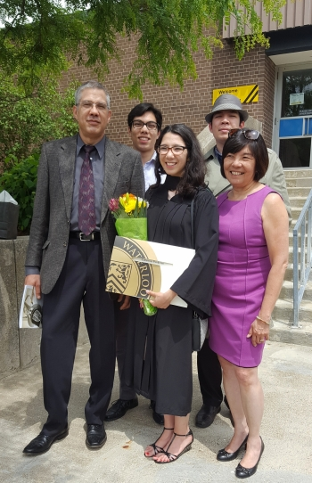 Catherine in graduation robes with her smiling family