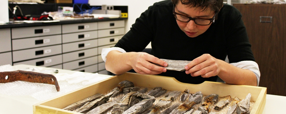 student in lab examines ancient wood artifacts