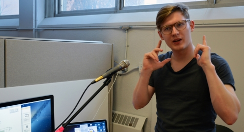 Student explains work in front of microphone