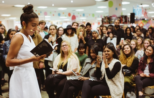 Rupi Kaur reading to smiling crowd