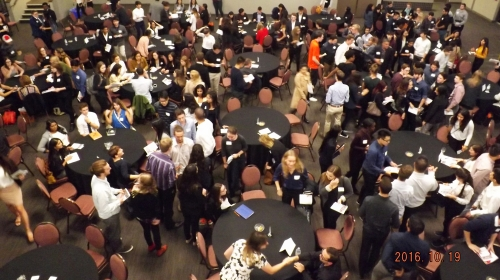large group of students networking around tables