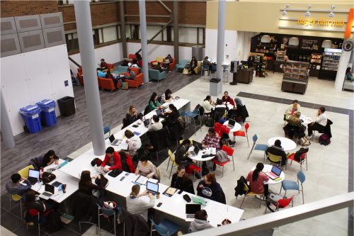 students sitting at counters and tables in hub main floor
