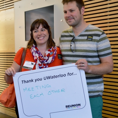 Couple holding sign saying they met at Waterloo